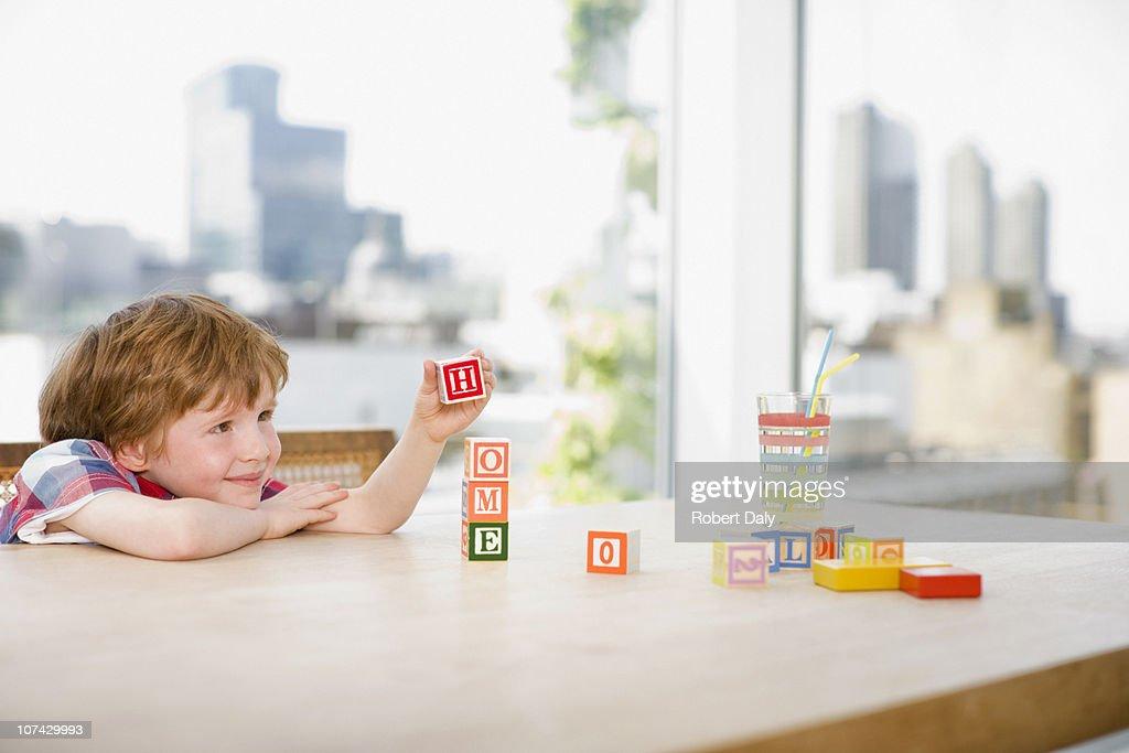 Boy stacking alphabet blocks that spell home : Stock Photo