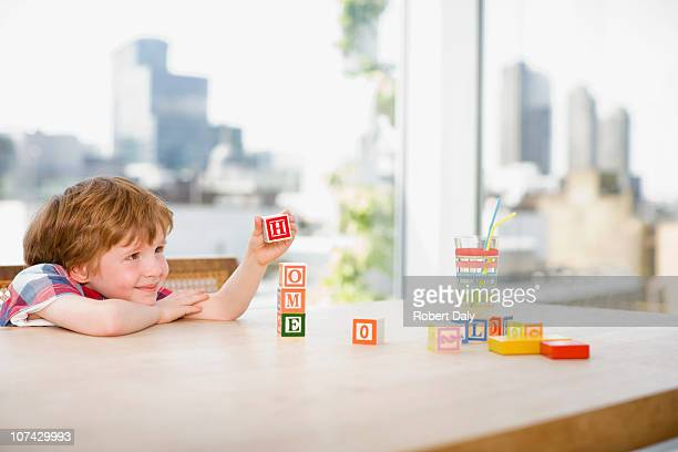 Boy stacking alphabet blocks that spell home
