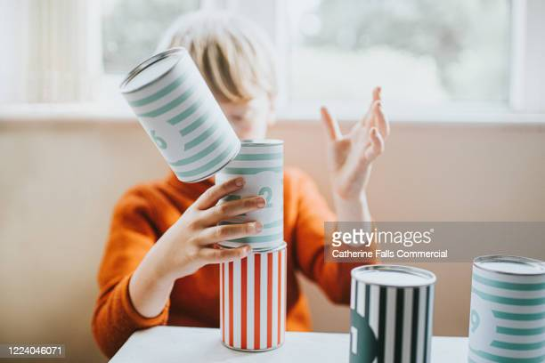 boy stacking cans - falling stock pictures, royalty-free photos & images