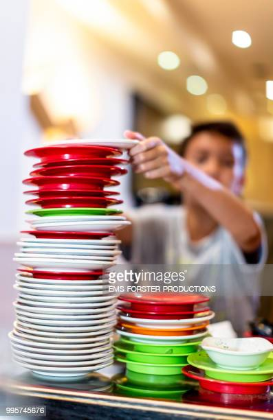 boy stacking plastic plates towering in sushi bar - child labour stock pictures, royalty-free photos & images