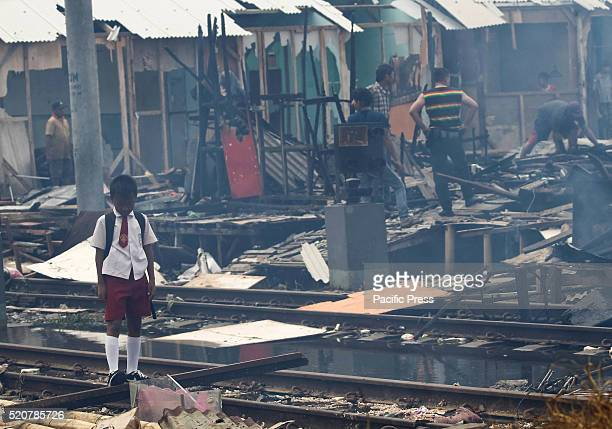 A boy stand amid the debris of his huts after a fire in a slum area next to railway tracks in Kampung Bandan Fire destroyed approximately 100 wooden...
