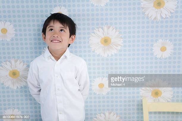 Boy (4-5 years) standing against floral wallpaper, studio shot