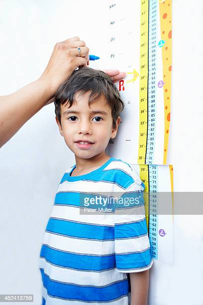 Boy standing against height chart being measured