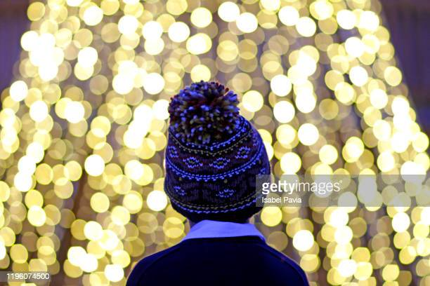 boy standing against illuminated lights - magician stock pictures, royalty-free photos & images