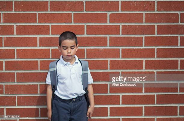 Boy standing against red brick wall after school