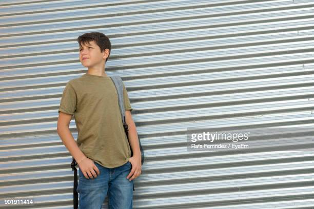 Boy Standing Against Shutter