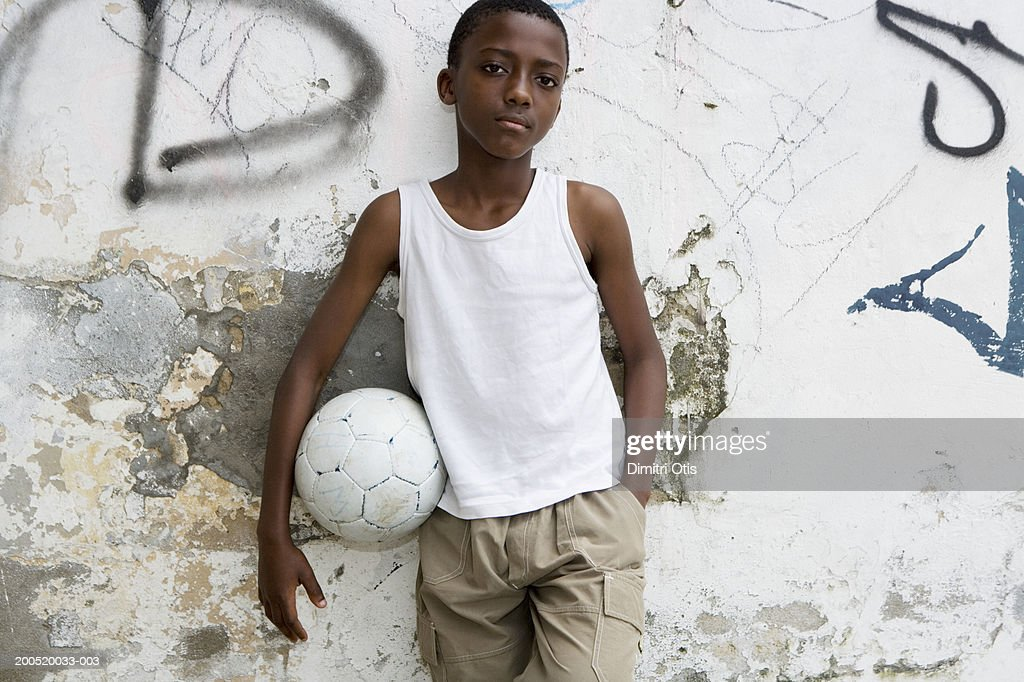 Boy (10-12) standing against wall, holding football, portrait : Stock Photo
