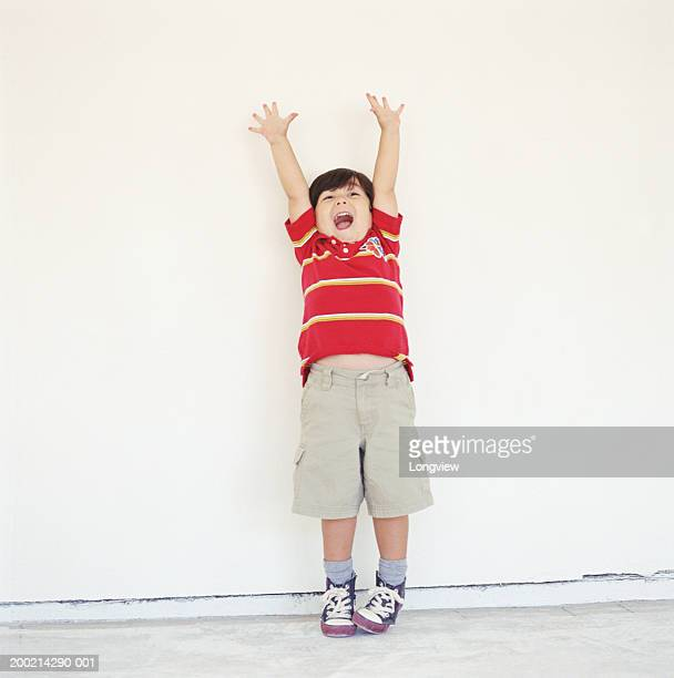 Boy (2-4) standing against wall, raising hands