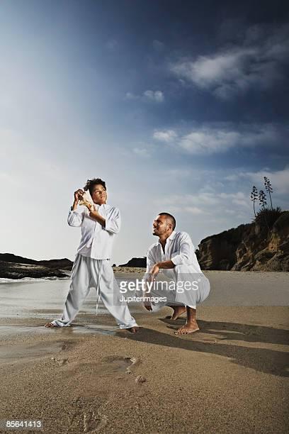 Boy standing and man squatting on beach