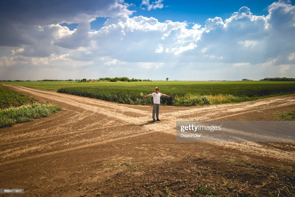 Boy Standing at Crossroad in Path : Stock Photo