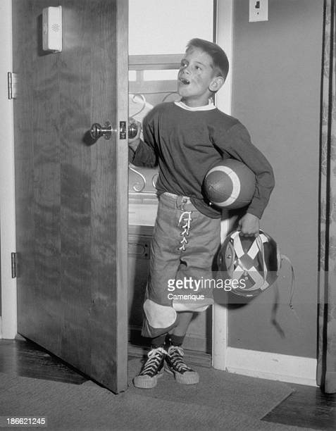 Boy standing at front door in full football gear holding football and helmet Philadelphia PA 1958