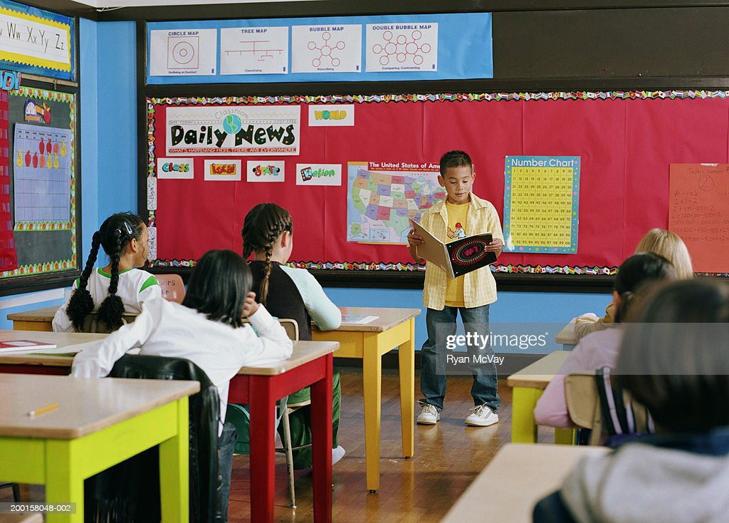 Boy (7-9) standing at front of classroom, giving presentation : Stock Photo
