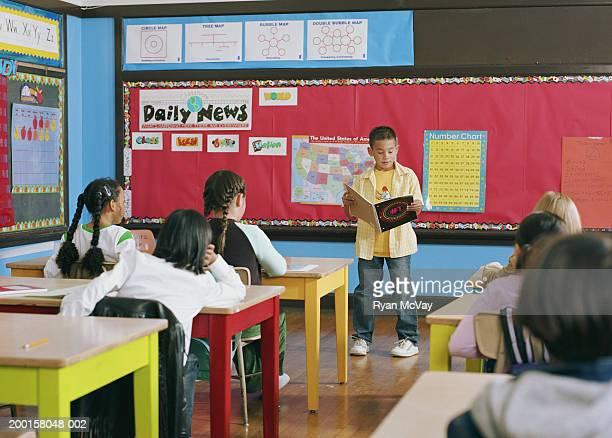 Boy (7-9) standing at front of classroom, giving presentation