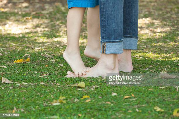 Boy standing barefoot and tiptoes on fathers feet