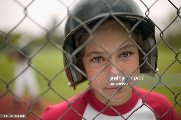 Boy (10-12) standing behind fence, portrait