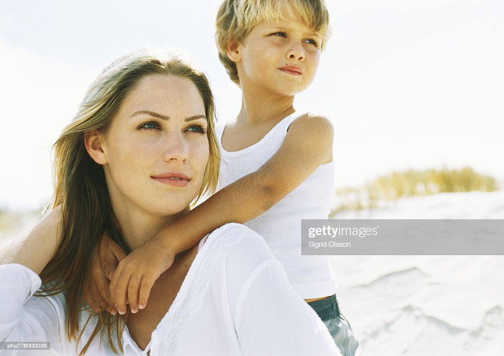 Boy standing behind seated mother on beach, portrait : Stockfoto