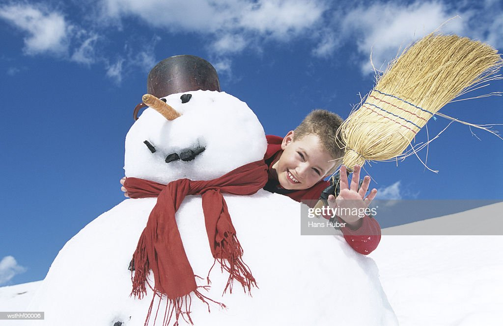 Boy standing behind snowman with broomstick : Stock Photo