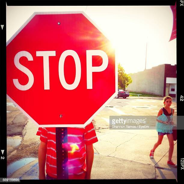 Boy Standing Behind Stop Sign On Street