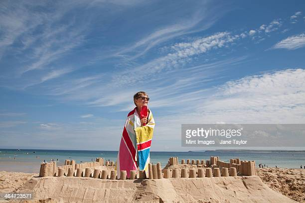 A boy standing beside a sandcastle,on top of a mound of sand. Beach.