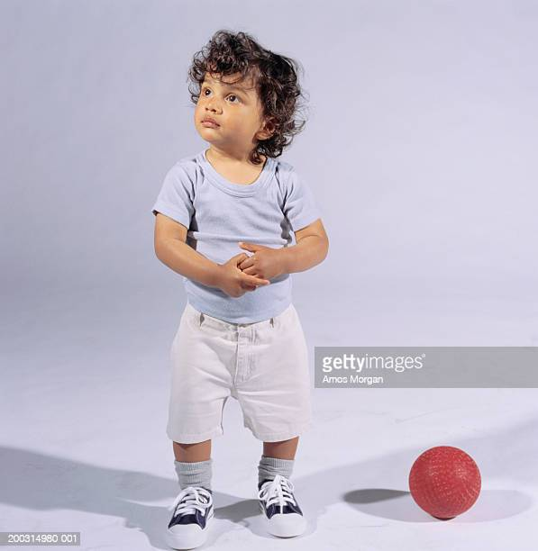 boy (12-13), standing beside ball, posing in studio, portrait - only boys stock pictures, royalty-free photos & images