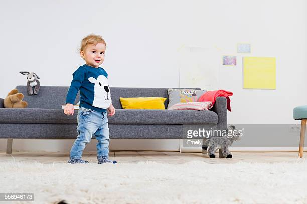 Boy standing beside sofa at home