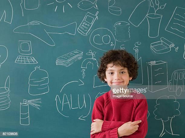 Boy standing by blackboard