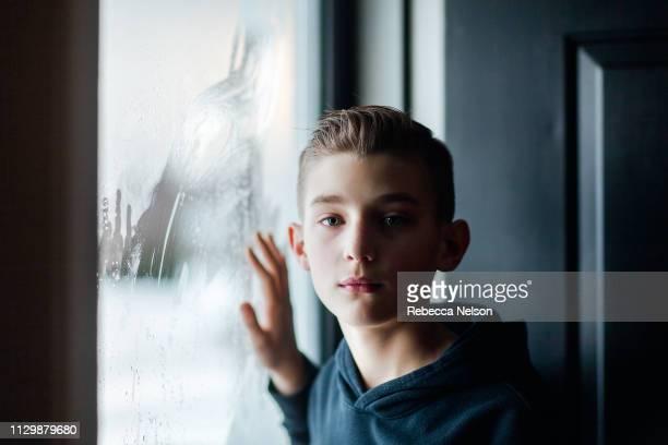 boy standing by glass storm door