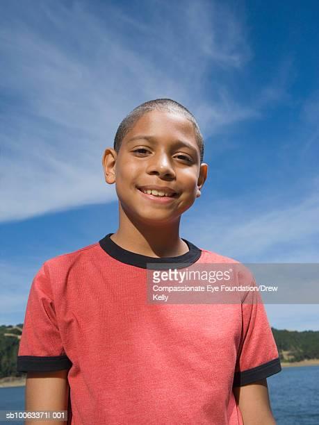 "boy (10-11 years) standing by lake, portrait - ""compassionate eye"" fotografías e imágenes de stock"