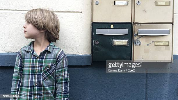 Boy Standing By Mailboxes Against Wall