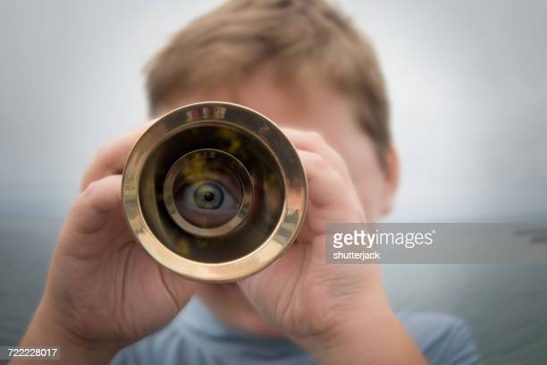 boy standing by ocean looking through a telescope - curiosity stock photos and pictures
