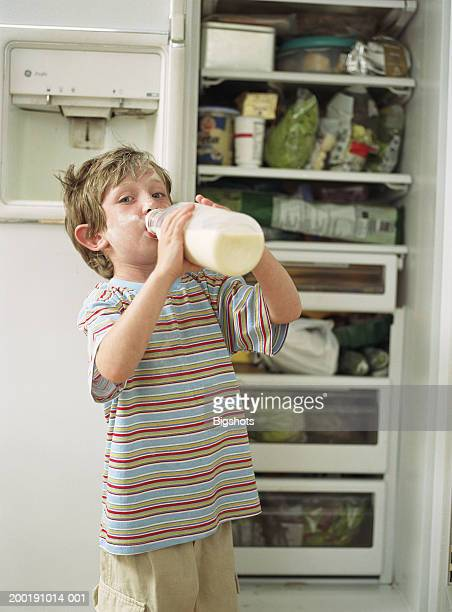boy (4-6) standing by open fridge drinking from milk carton, portrait - milk carton fotografías e imágenes de stock