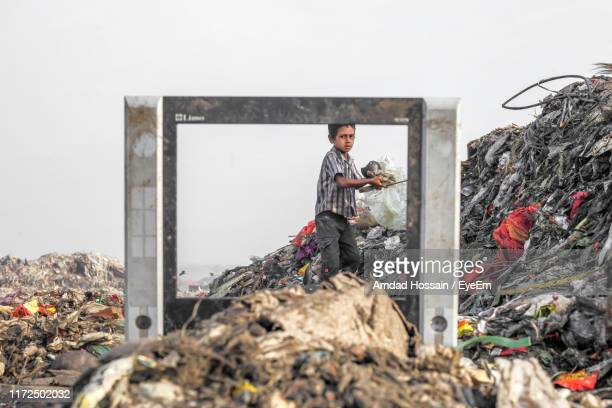 boy standing by pile of garbage seen through metal against sky - チッタゴン ストックフォトと画像