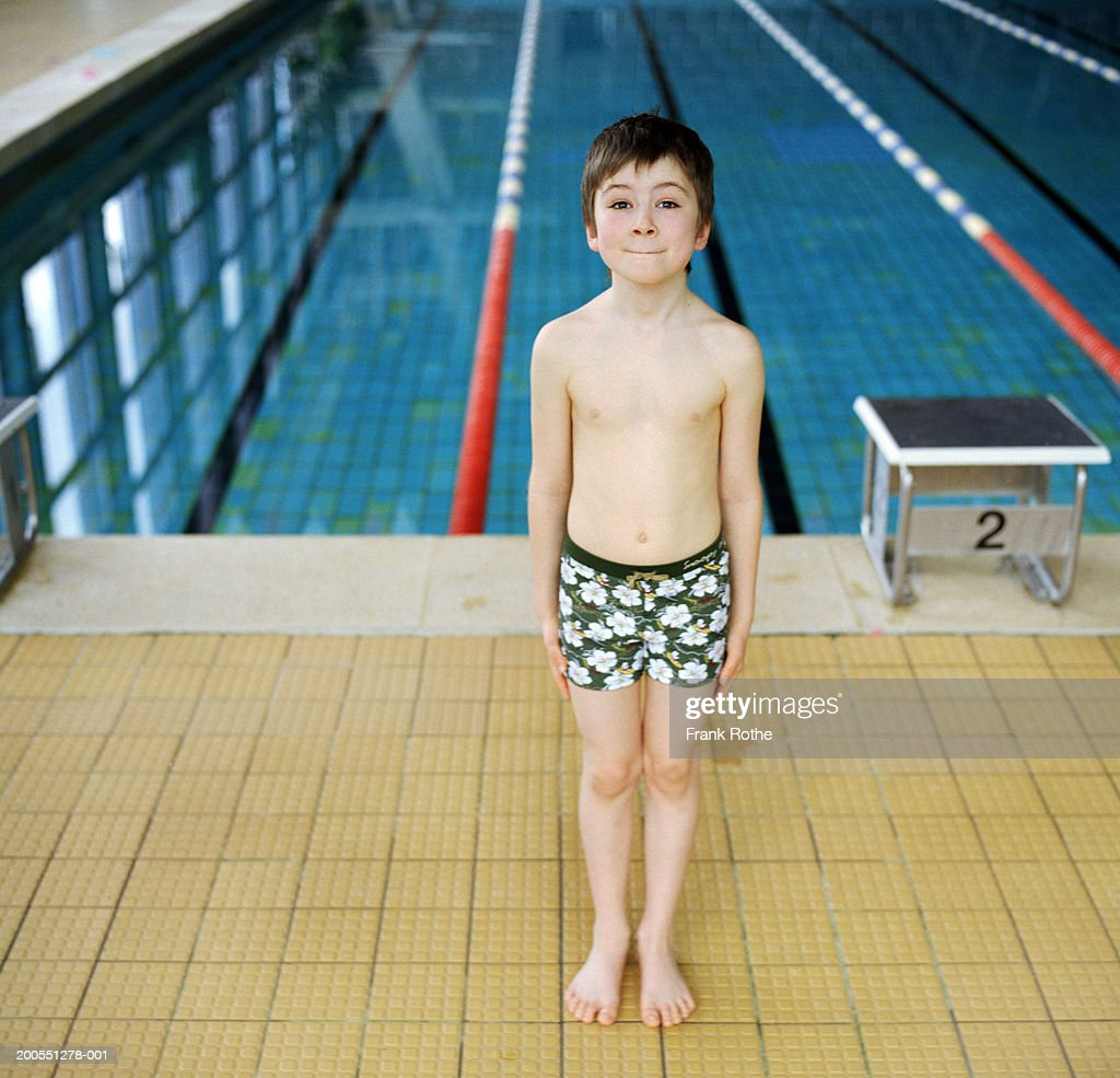 Boy (6-7) standing by swimming pool, portrait : Stock Photo
