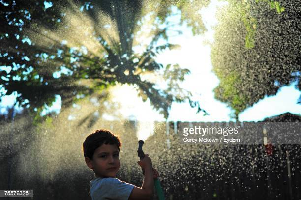 Boy Standing By Tree Against Water