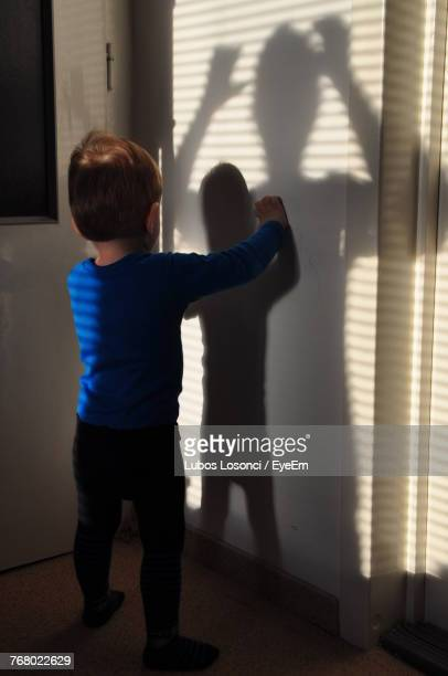 Boy Standing By Wall At Home
