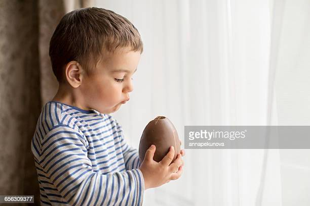 Boy standing by window eating a large chocolate easter egg
