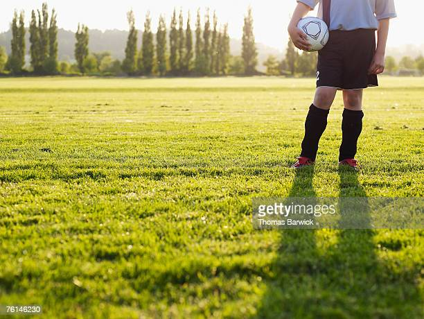 Boy (10-11) standing holding football in field, low section