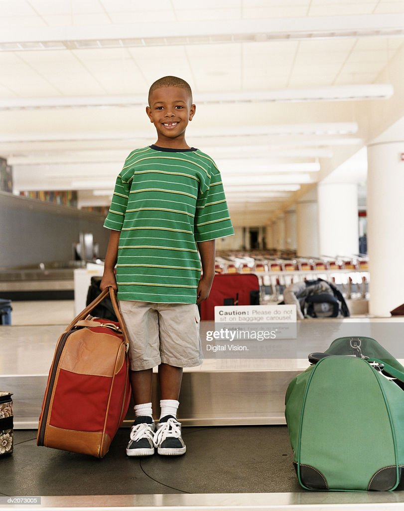 Boy Standing Holding Luggage on an Airport Baggage Conveyor Belt : Stock Photo
