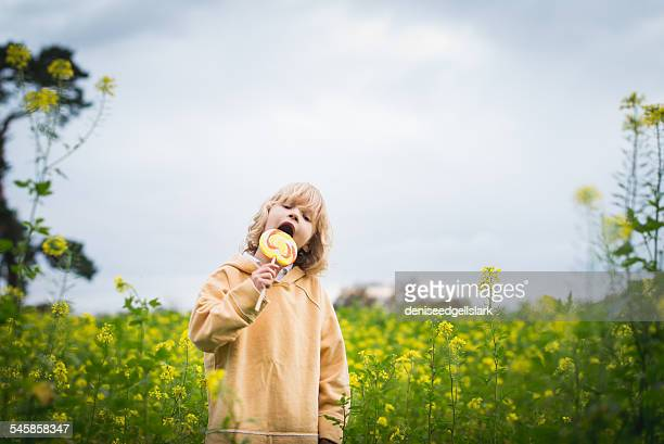 Boy standing in a field eating a lollipop