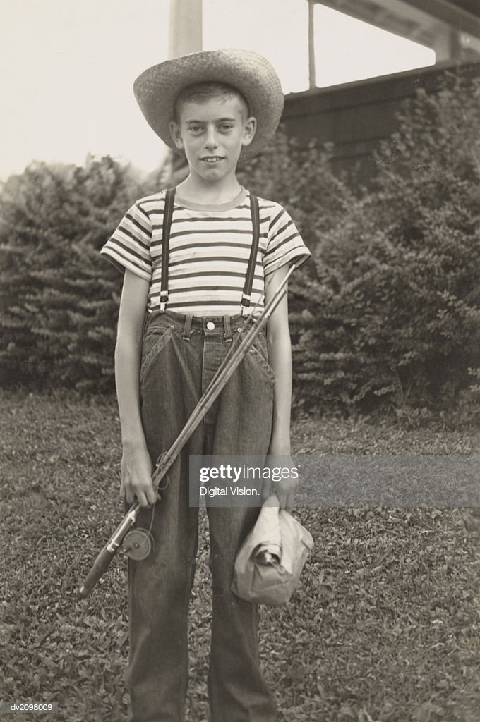 Boy Standing in a Garden Holding a Fishing Rod : Stock Photo