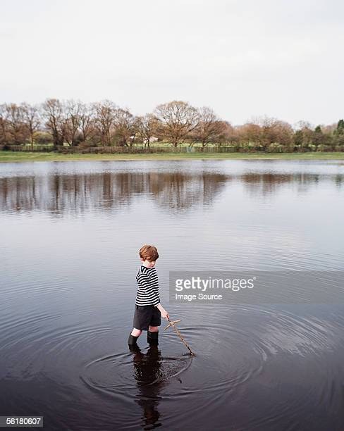 boy standing in a lake - waist deep in water stock pictures, royalty-free photos & images