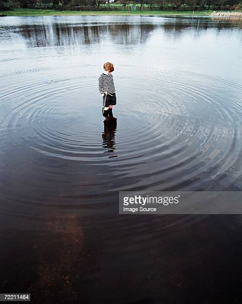 boy standing in a lake - rippled stock pictures, royalty-free photos & images