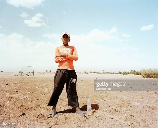 boy standing in barren football field - ルポルタージュ ストックフォトと画像