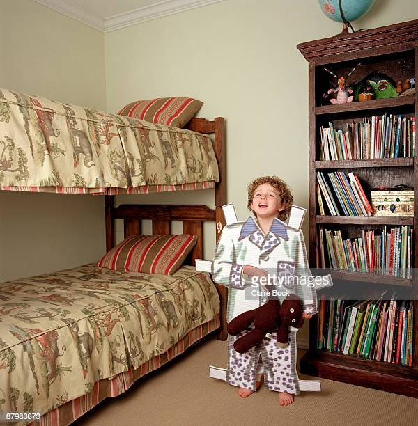 Boy standing in bedroom in paper doll pajamas