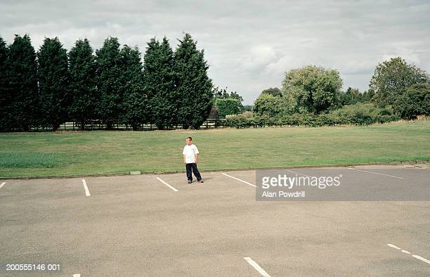 Boy (12-13) standing in empty parking lot with hands in pockets, elevated view