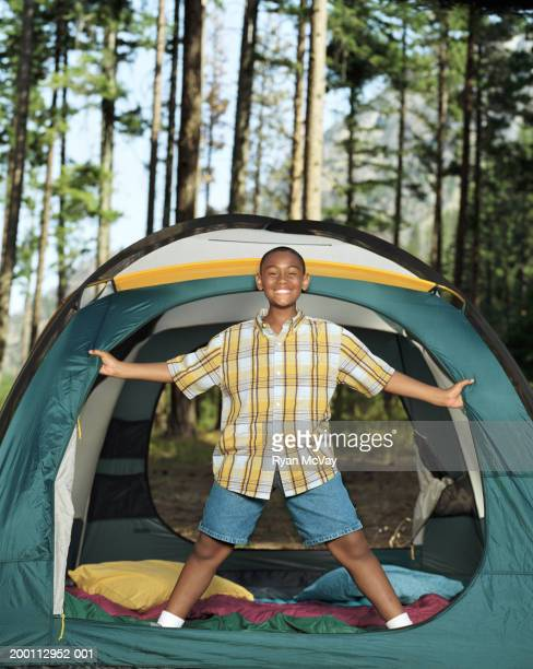 Boy (10-12) standing in entrance to tent, portrait