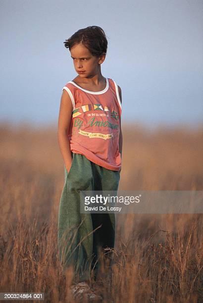 boy (8-11) standing in field, looking over shoulder - hände in den taschen stock-fotos und bilder
