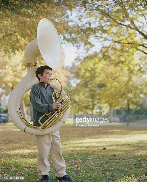 Boy (8-10) standing in field, playing tuba, autumn
