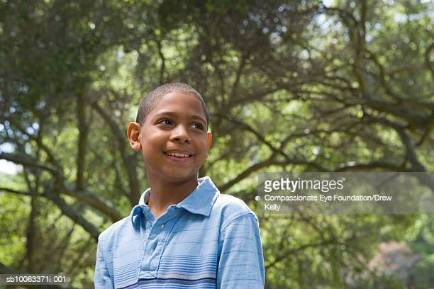 """boy (10-11 years) standing in forest, low angle view - """"compassionate eye"""" fotografías e imágenes de stock"""