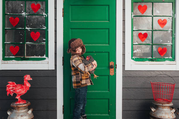Boy standing in front of a chicken coop hugging a chicken, USA